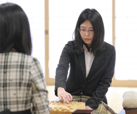 4手目を指す里見香奈女流名人。手前は挑戦者の伊藤沙恵女流二段