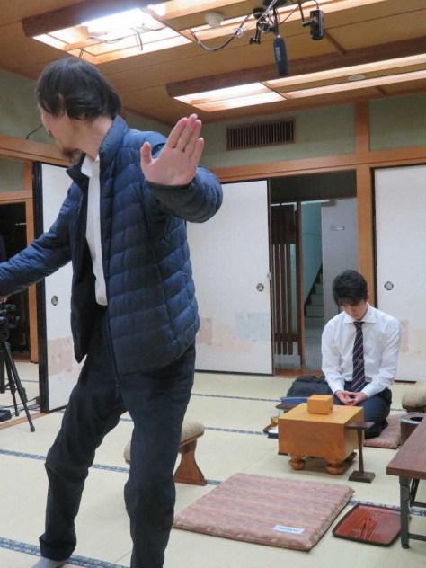 大阪市の関西将棋会館での順位戦C級1組2回戦。堀口一史座七段が対局場入りの際、報道陣のカメラに向かって踊るようなポーズ。奥は静かに待つ藤井聡太七段