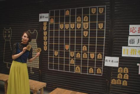 愛知県瀬戸市の「せと銀座通り商店街」では店舗のシャッターにある大きな将棋盤と飯島加奈さん(撮影・松浦隆司)