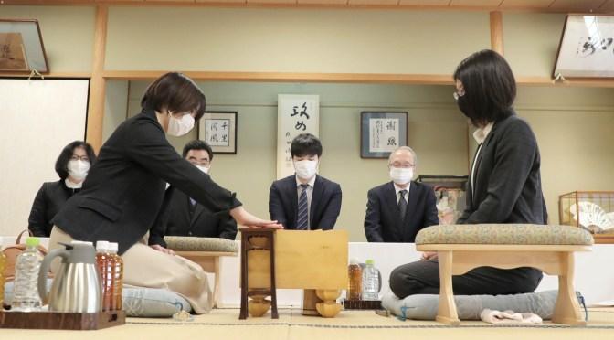 初手を指す挑戦者の加藤桃子女流三段(手前左)。同右は里見香奈女流名人(カメラ・関口 俊明)