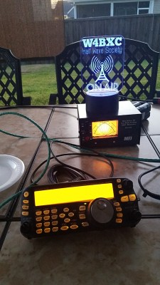 Evening radio station illumination provided by the radio, SWR meter, and W4BXC edge lit acrylic sign.