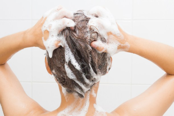 Woman washing her hair on white tiles background.
