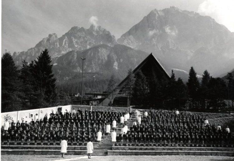 foto storica con in primo piano i figli degli operai Eni in villeggiatura a Corte di Cadore, in secondo piano la colonia, sullo sfondo le montagne.