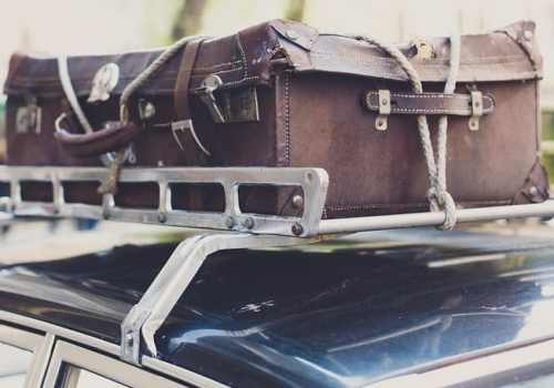 Vintage suitcase on a car roof.