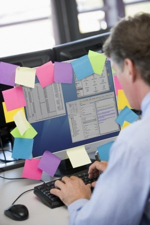 Office worker at computer covered in sticky notes