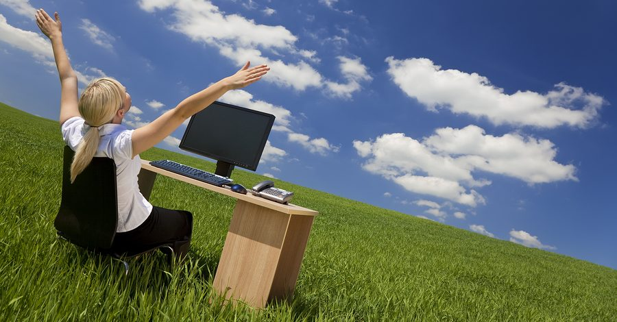 Business concept shot of a beautiful young woman sitting at a desk using a computer in a green field raising her arms into a bright blue sky with fluffy white clouds, symbolizing rapid adoption of cloud CPM software.