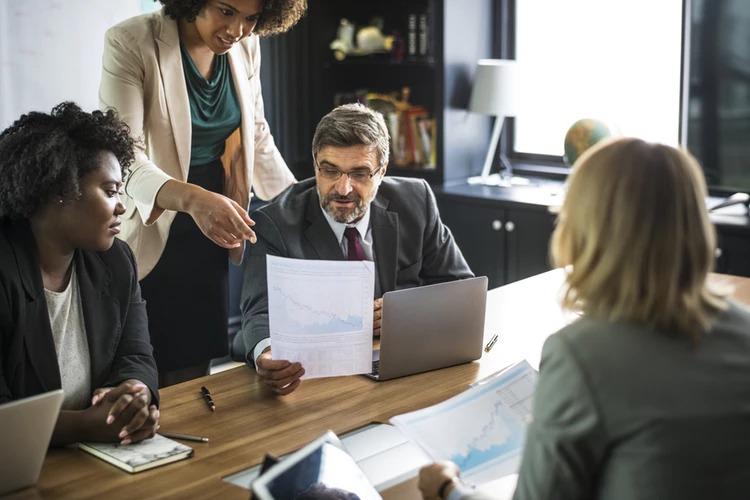 Alguns advogados analisando métricas e dados em um gráfico para performar mais em escritórios de advocacia