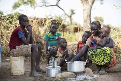 Sudanese refugee, Amal Bak, and children get their first breakfast of good food after weeks of rotten food and a seven day journey to a refugee camp at Aluong Thok in Southern Sudan.