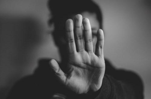 osoba wystawiająca otwartą dłoń, która zakrywa jej twarz
