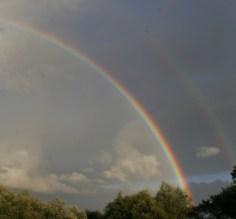 Foto, Wolken mit einem Regenbogen