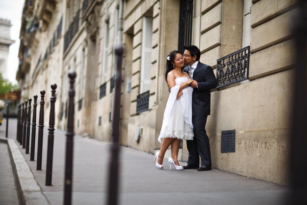 Fotografia de noivos em ensaio urbano. Os noivos estão de pé e uma rua com estilo arquitetônico antigo.