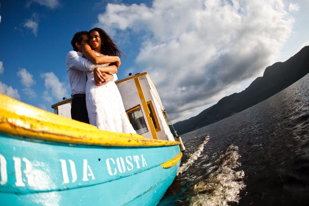 Foto de ensaio fotográfico com noivos abraçados em um barco, seguindo travessia no mar e com a luz realçando o sorriso da noiva que está de vestido branco.