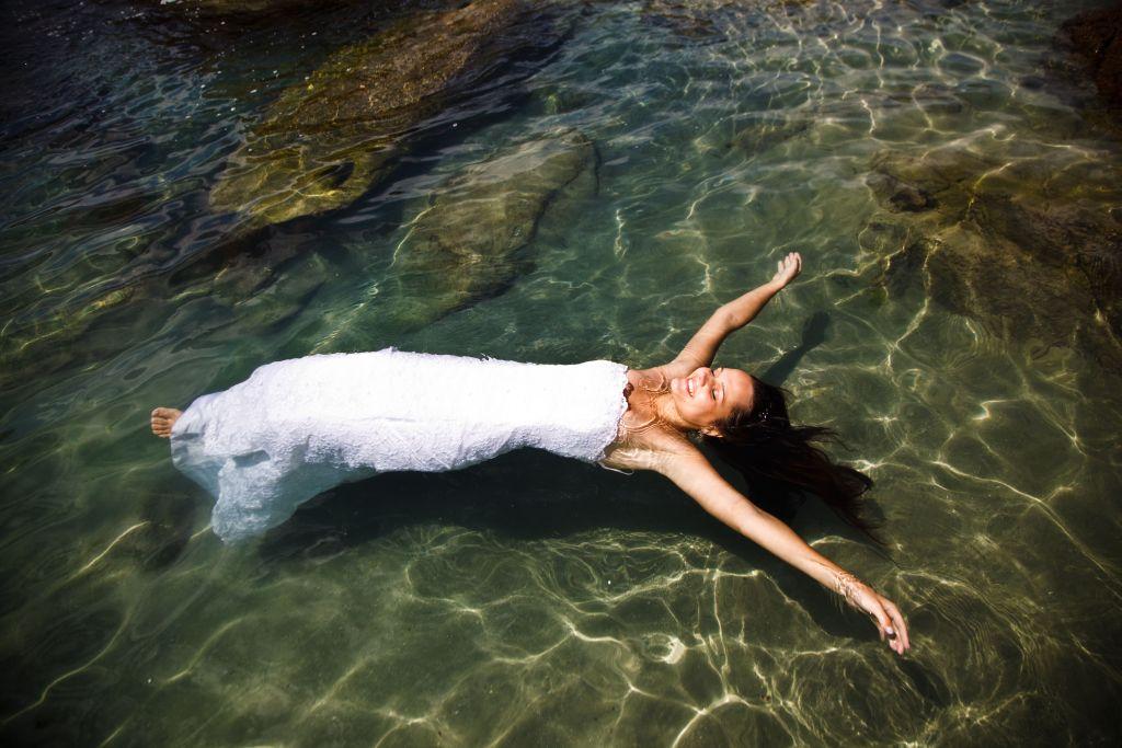 Noiva, com longo vestido branco, flutuando no mar em ensaio fotográfico com os braços abertos.