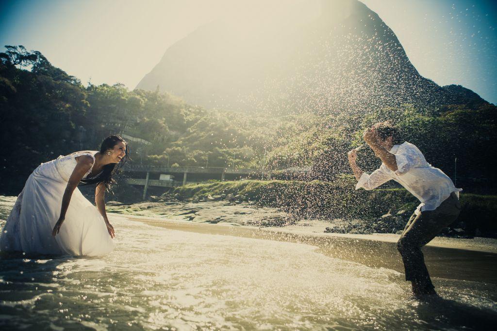 Noivos brincando na agua do mar em fotografia pós casamento.