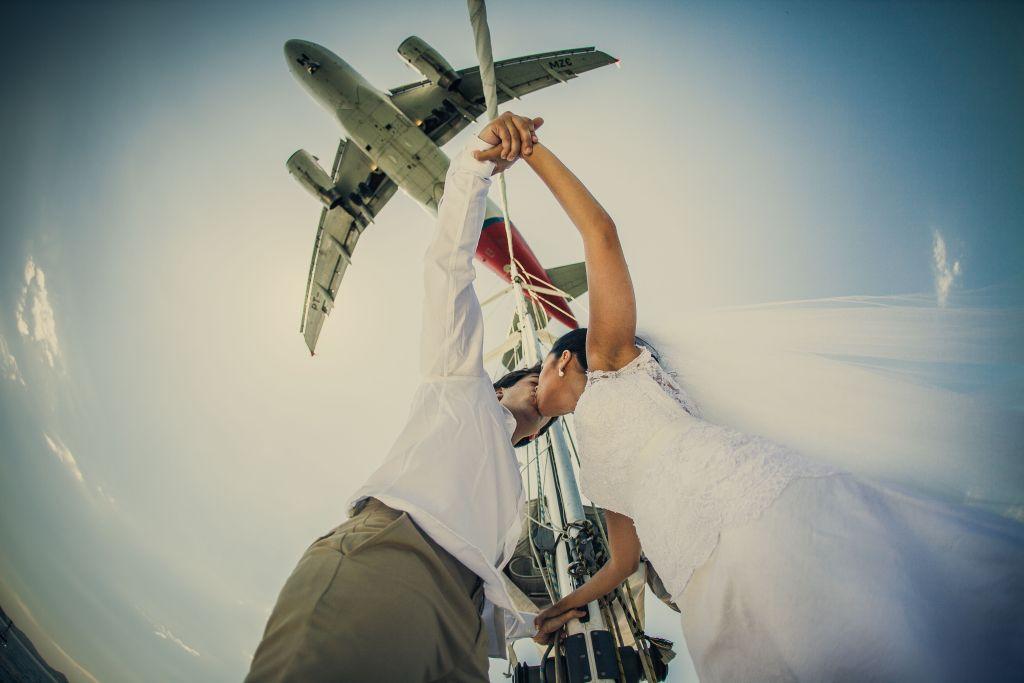 Ensaio fotográfico com noivos se beijando em um dia ensolarado e com um avião no céu.