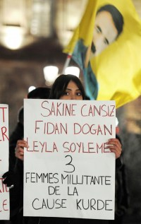 "A woman of Kurdish origin holds a sign reading ""Sakine Cansiz, Fidan Dogan, Leyla Soylemez - 3 women militants of the Kurdish cause"" during a demonstration and commemoration in honor of the three Kurdish women activists killed yesterday in Paris, on January 10, 2013."