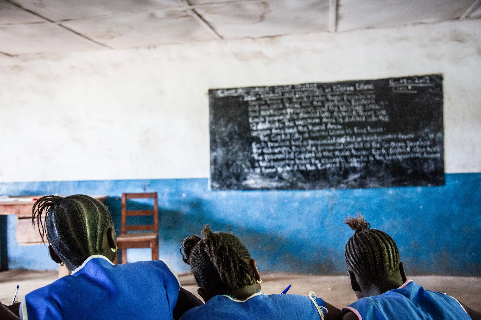 Anonymous school children, all girls, in front of a blackboard at an unidentified school somewhere in Sierra Leone.