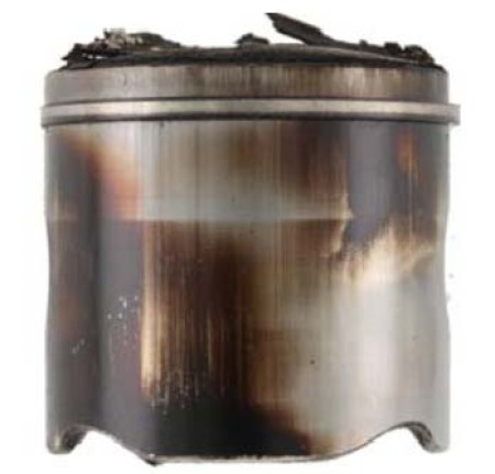 The piston crown and skirt contain deposits. Excessive deposits reduce efficiency and can lead to engine failure.