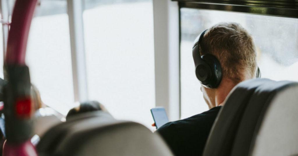 Homem descansa ouvindo música em traslado de eventos corporativos
