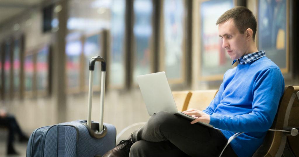 Homem em um aeroporto trabalhando enquanto espera o voo, ilustrando uma rotina de gestão de tempo em viagens corporativas