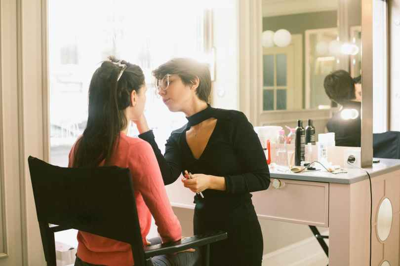 Young female make-up artist with her client
