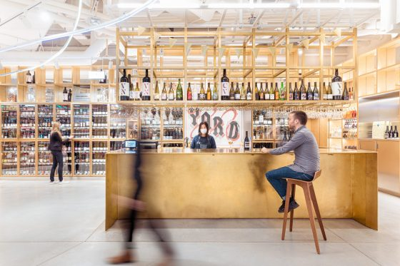 Le bar en laiton se trouve devant des frigos qui présentent toutes les bouteilles