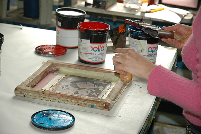 A screenprint artist at work. (Photo via Wikimedia Commons)