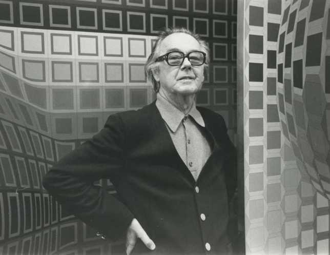 photograph of Victor Vasarely in front of his artworks