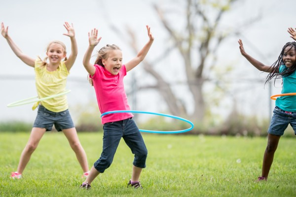 three girls hula hooping outside