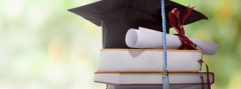 Graduation hat with degree paper on a stack of book against blurred background