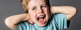 screaming young boy covering his ears grey background
