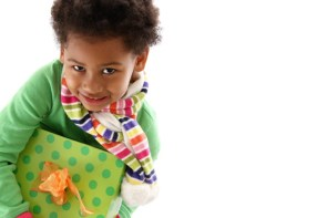 young child in green sweater holding wrapped present and smiling up at camera.