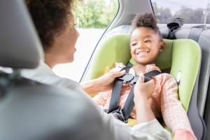 A preschool age girl looks at her mother and smiles as she is buckled into her car seat.