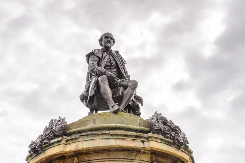 Statue of William Shakespeare seated on a pedestal, seen from low ground angle