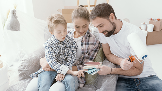 Happy family renovating their home and painting rooms: the boy is picking a new color for the house rooms - finance a home renovation