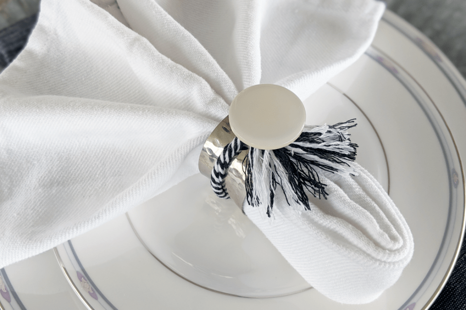Large white button accents silver napkin ring with black white tassel.
