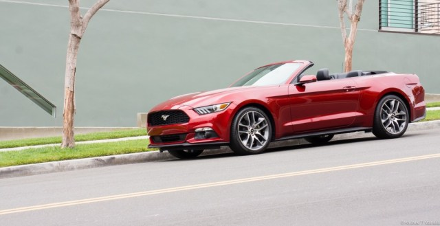 A Cherry Red Ford Mustang convertible parked on the street.