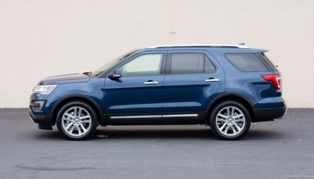 A Dark Blue Ford Explorer parked in front of a white wall.