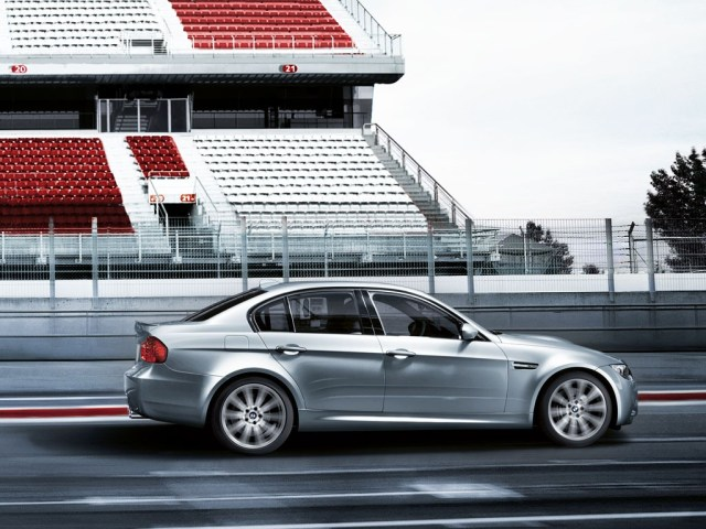 side view of a silver 2009 BMW M3 sedan at the track.