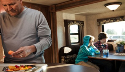 4 stove top recipes for rv cooking, picture of a man cooking in his rv for his family