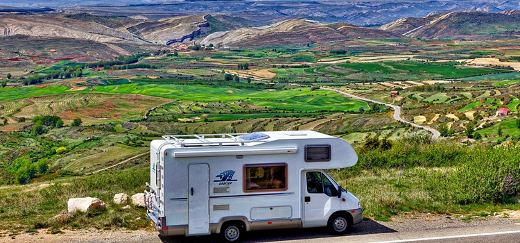 go rving for your family vacation, go rving, picture of a motorehome on the side of the road rving and looking at a gorgeous scenery