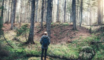 7 ways to slow down and connect with nature, picture of a women standing with a backpack on in a beautiful forest with the sun shining through the trees