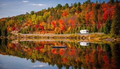 picture to visit norway maine with a lake and color changing trees in the background