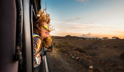 Beautiful caucasian young woman living the RV life. Head outside the RV with wind in the curly hair, motion and movement on the road discovering new places during a nice sunset, enjoy and joyful freedom concept