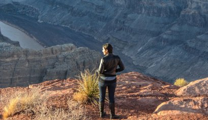 Woman standing on West Rim Trail, Grand Canyon Village one of the greatest places to hike in the United States.