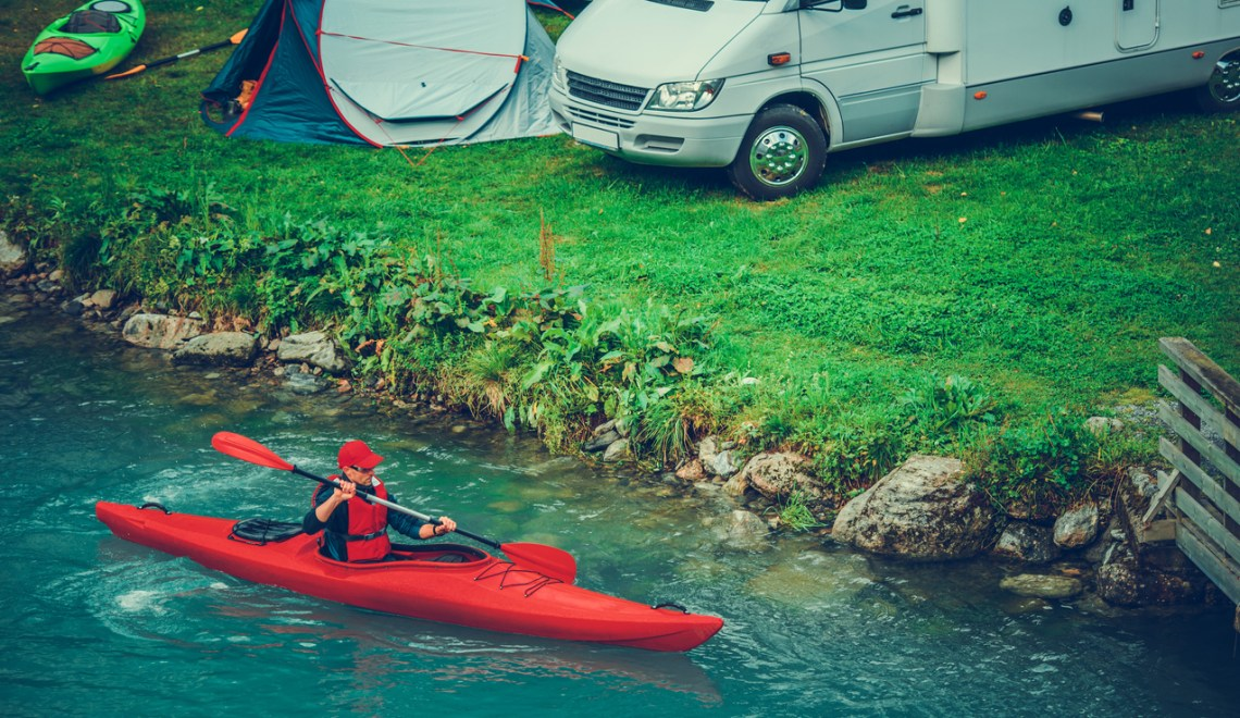 Waterfront RV and Tent Camping with Kayaking. Caucasian Sportsman RVing with a Kayak on Glacial Lake.