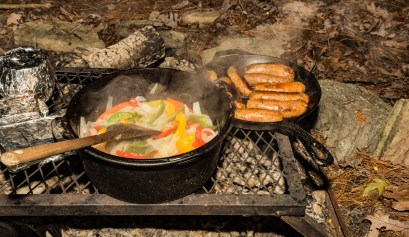 Cooking sausage and vegetables on the campfire with campfire recipes