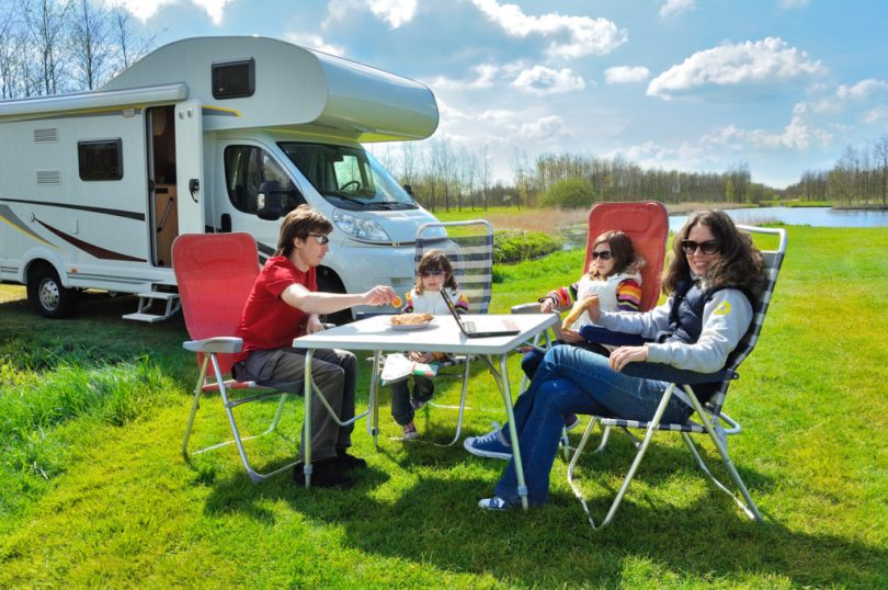 Family sitting and enjoying their meals while camping outside of their RV.