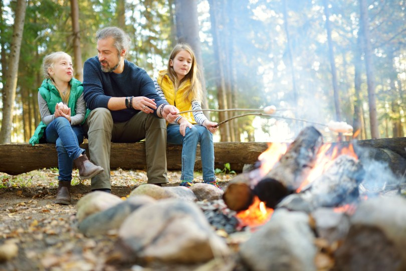 Father and his kids in a campsite cooking their food using wood.