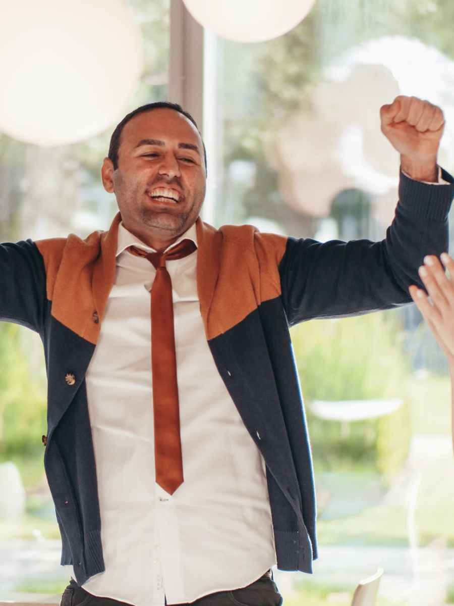 crop cheerful multiethnic colleagues celebrating victory in office